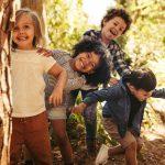Neljä lasta hassuttelee metsäisessä ympäristössä.
