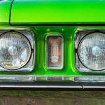 Kirkkaan vihreän retroauton keulan ajovalot lähikuvassa.