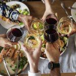 Ystävykset kohottavat viinilaseja ruokien yllä.