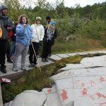 Ihmisiä katsomassa Alta kalliomaalauksia