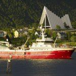 Kalastusalus Tromssan edustalla, taustalla näkyy Jäämerenkatedraali.