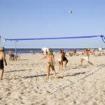 Ihmisiä pelaamassa rantalentopalloa aurinkoisena päivänä.