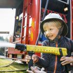 Pieni poika kypärä päässä ruiskuttaa vettä paloauton letkusta.