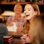 Mies ja nainen nauravat olutlasit käsissään baaritiskin edessä.