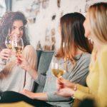 Kolme ystävystä istuvat viinilasillisella.