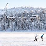 Hiihtäjiä jäällä, taustalla rakennuksia rinteessä sekä mäkihyppytorni.