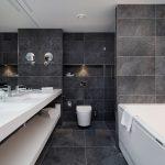 Puistosviitin kylpyhuoneen seinälaatat ovat tyylikkään tumman harmaat