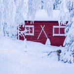 Punainen hirsimökki ja laskettelija lumisessa maastossa.
