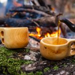 Kahvipannusta kaadetaan puisiin kuksamukeihin kahvia nuotion äärellä.