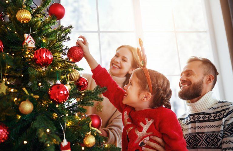 Hymyilevä pieni tyttö poronsarvipanta päässään ripustaa joulukoristeita kuuseen vanhempiensa kanssa.