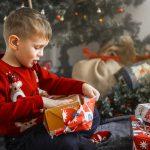 Punaiseen poropaitaan pukeutunut pieni poika avaa joulupakettia haltioitunut ilme kasvoillaan.