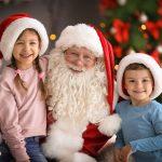 Pieni tyttö ja poika istuvat tonttulakit päässään joulupukin sylissä.