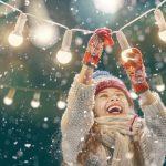 Innostunut pieni tyttö ripustaa koristevaloja lumisateessa.