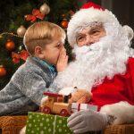 Pieni poika kuiskuttaa joulupukin korvaan joulukuusen edessä.