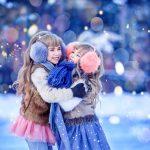 Kaksi pientä tyttöä juhlavissa vaatteissa isot korvalaput päässään halaavat nauraen.
