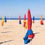 Värikkäitä päivävarjoja hiekkarannalla.