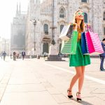 Vihreämekkoinen nuori nainen aurinkolasit päässään kantaa ostoskasseja hymyillen Duomon aukiolla.