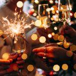 Juhlivat ystävykset pitävät kädessään kuohuviinilaseja ja tähtisadetikkuja.