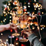 Ystävykset kilistävät kuohuviinilaseja joulukuusen edessä.