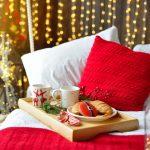 Sängylle aseteltu tarjotin, jossa jouluisia herkkuja.