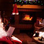 Joulupukki lukee kirjettä takkatulen ääressä.