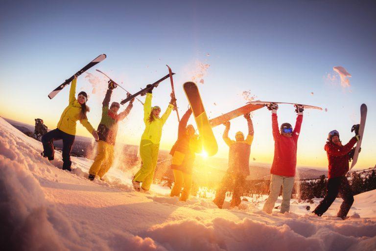 Ryhmä iloisia laskettelijoita nostaneet lasketteluvälineet ilmaan auringon laskiessa.