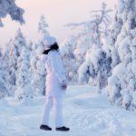 Valkoiseen toppa-asuun pukeutunut nainen nauttii luonnonrauhasta lumisen metsän keskellä.