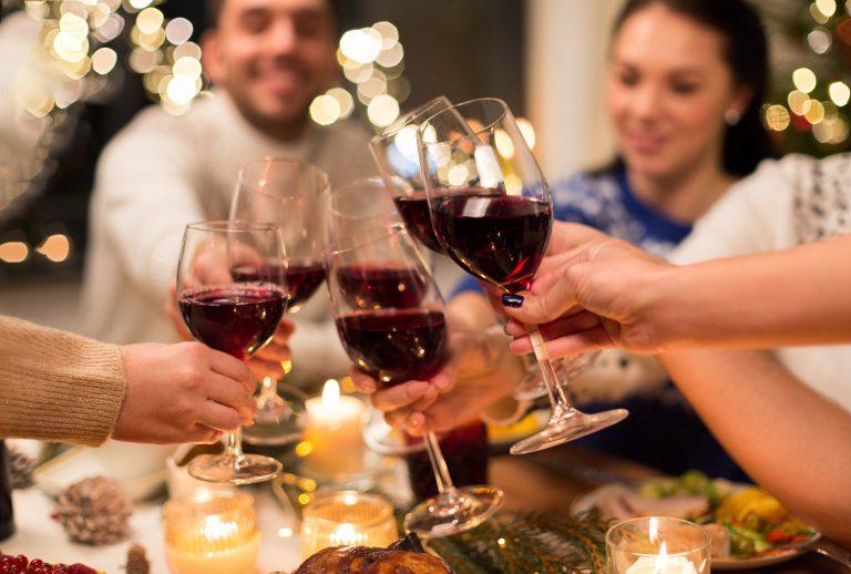 Ystävykset kohottavat viinimaljoja katetun joulupöydän ääressä.