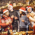 Kaveriporukka juhlimassa joulua tonttulakit päässä katetun ruokapöydän edessä.