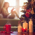 Nuori nainen lukee ikkunan edessä, etualalla joulukuusi, höyryävä kuppi ja kynttilöitä.