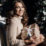 Nuori nainen istuu lattialla lahjapaketti sylissä ja hymyilee onnellisena.
