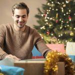 Hymyilevä nuori mies istuu lattialla ja tutkii lahjapaketteja.