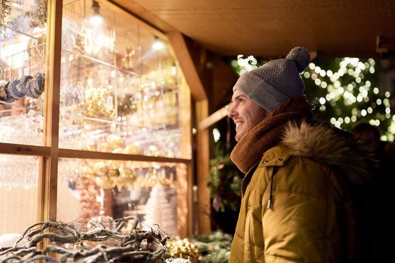 Talvivaatteisiin pukeutunut mies hymyilee ja katsoo näyteikkunaa.