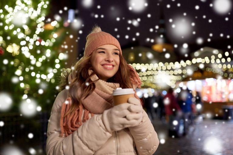 Lämpimästi pukeutunut nuori nainen hymyilee kuppi kädessä jouluvalaistulla kadulla.