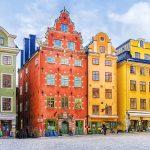 Värikkäitä keskiaikaisia taloja rivissä torin laidalla