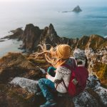 Nainen istuu reppu selässä kallioilla ja ihailee maisemaa merelle.