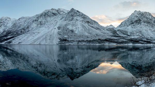Tummansävyiset lumiset alpit veden äärellä