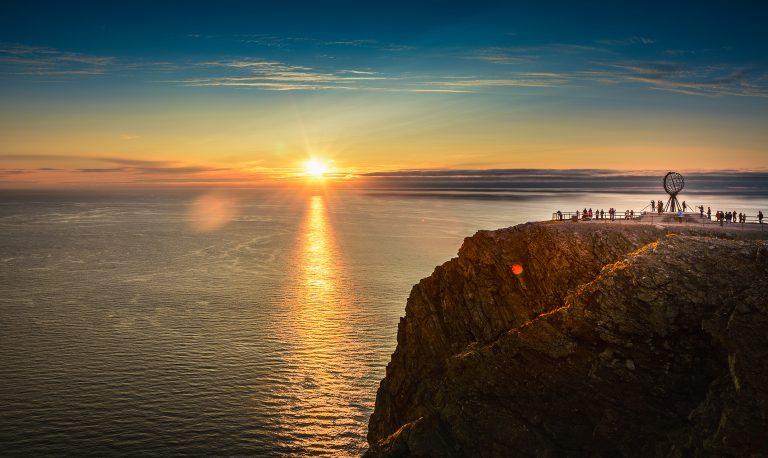 Ihmisiä ihailemassa keskiyön aurinkoa Nordkapissa.