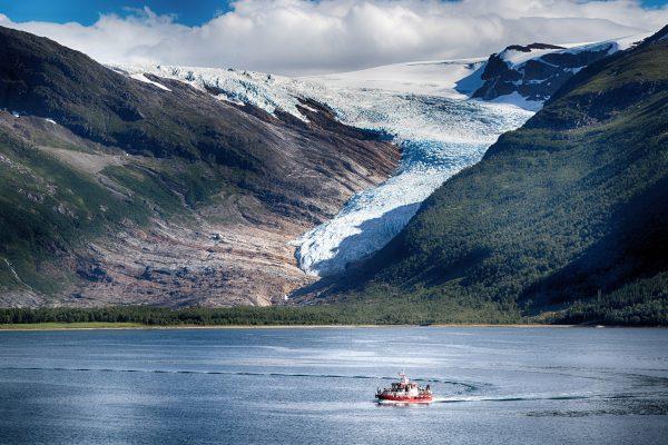 Vene seilaa jäätikön edustalla