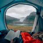 Näkymä teltasta kohti Svartiseniä. Henkilö makoilee kirja kädessä ja katsoo maisemaa.