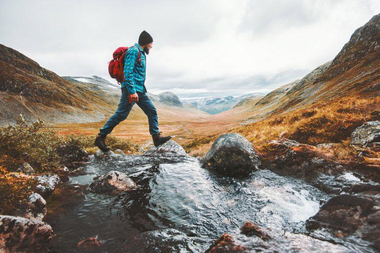 Mies ylittää puroa vaelluksella vuoristossa.