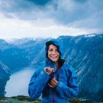 Nainen hymyilee ja sulkee sinistä sadetakkia vuorella.