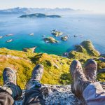 Kaksi henkilöä istuu meren yllä kalliolla vaelluskengät jalassa.