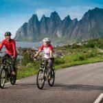Mies ja nainen pyöräilevät iloisina, taustalla Tungenesetin terävät vuorenhuiput.