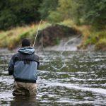 Mies kalastaa kahluuhousut jalassa joella.