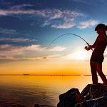 Nuori nainen kalastaa ilta-auringon paistaessa.