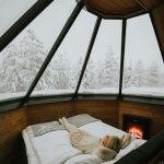 Nainen ihailee talvimaisemaa lasikattoisessa iglussa sängyllä makoillen