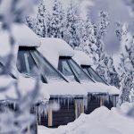 Lasikattoisia revontulimökkejä rivissä talvipäivänä