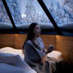 Nainen istuu revontulimökin sängyn reunalla muki kädessään ja viltti harteillaan.