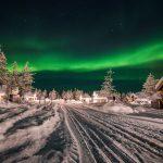 Northern Lights Village Levin mökkejä talvella luminietsoten keskellä revontulien alla